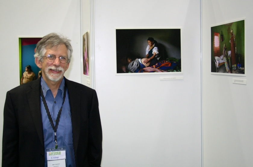 Mark standing in front of his photo exhibit at Women Deliver 2013