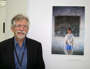 Mark standing in front of one of his photos with a positive story about girls & education