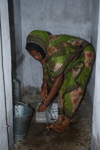 Gram Vikas-Woman cleaning the toilet room