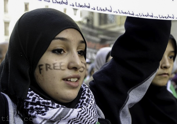 "Image courtesy of Freedom House/Flickr. A young woman with the words ""Free Syria"" written on her face attends a demonstration against violence in Syria on February 26, 2012 in Madrid"