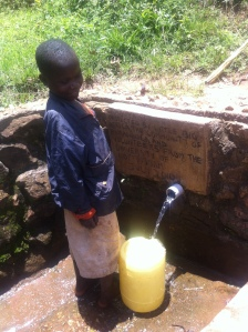 A young girl collecting safe water from a source that LBA has protected. Photo Credit: Eleanor Gall