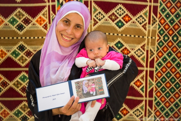A Syrian woman holds a framed photo that she plans to send back to family members still in Syria, who have never seen her baby girl.  For a moment, she is reminded that home is far more than just a place.  Photo by Annie Griffiths.