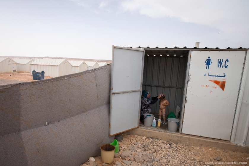 A child is washed in an outhouse in a UNHCR refugee camp in Jordan. Being together as a family gives them hope.  The family was caught between ISIS and the Syrian regime, forcing them to flee. They are deeply saddened by the thought that they might never go home, but know their current situation is better than the last.  Photo by Lynn Johnson.