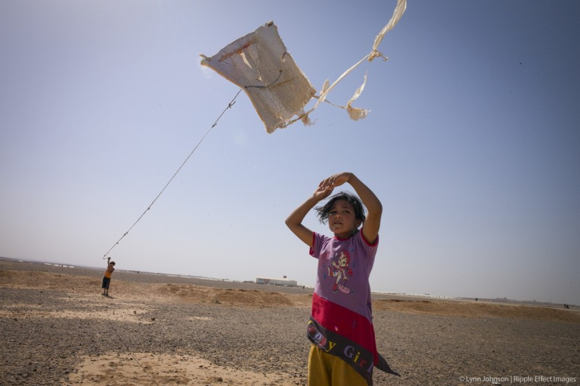 """Officially, these children are two of many asylum seekers. Unofficially, they are kite makers and kite flyers. Kites in this refugee camp are more than soaring bits of refuse made of insulation, plastic bags, and string snagged from the rubbish bin—they're creations to be proud of. It's simple really, as one child said, """"When the kite is flying, I am flying.""""  Photo by Lynn Johnson."""