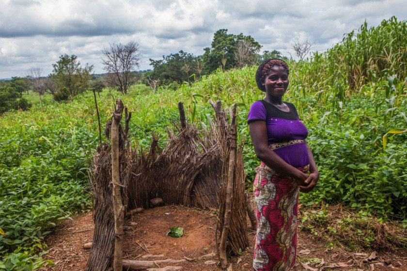 Kadoon Tilenene, 21 , farmer by their community open pit toilet in Agaku. Agaku is one of the communities in Benue that lack clean water supply. Their main water source is the river and rainfall. Open defecation is widely practiced in Agaku. Photo by WaterAid/Andrew Siebo