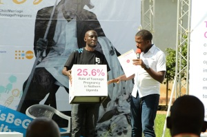 Reach a Hand, Uganda Team leader Humphrey Nabimanya giving a perspective of the rates of teenage pregnancy in the country to the audience during one of the community dialogues.