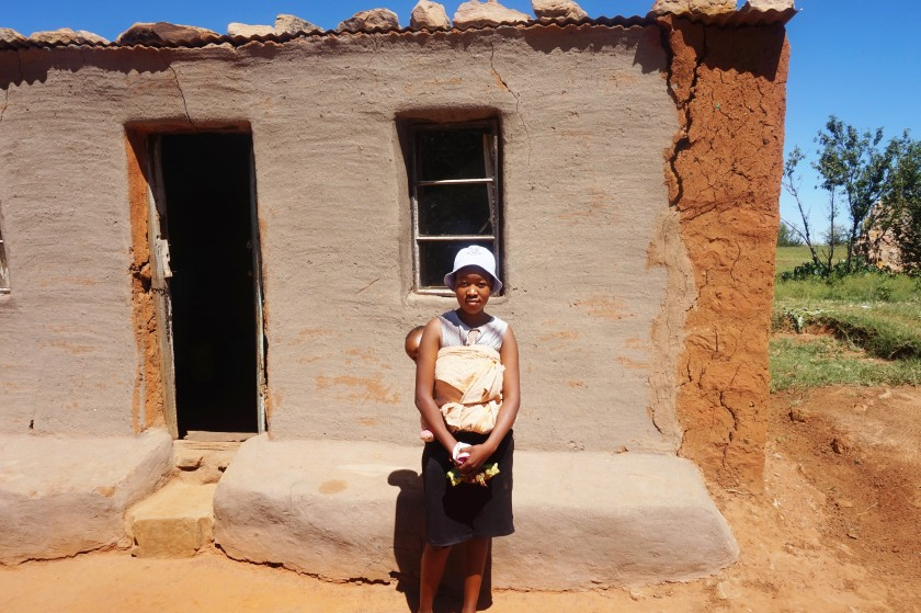 Puleng standing outside of her house